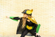 Girl in super heroine costume posing at brick wall - ERRF01028
