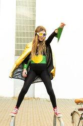 Girl posing in super heroine costume on bicycle rack - ERRF01031