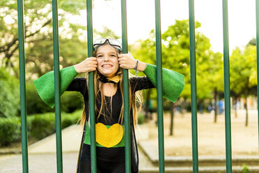 Happy girl in super heroine costume behind bars - ERRF01040