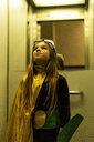 Girl in super heroine costume in elevator looking up - ERRF01052