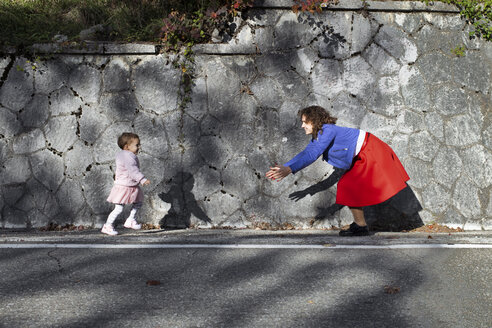 Little girl running to her mother at a stone wall - EYAF00136