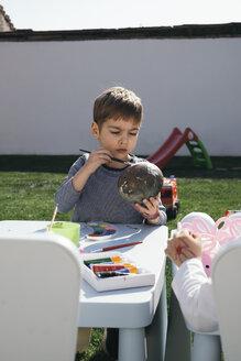 Boy painting Easter egg in garden - MOMF00688