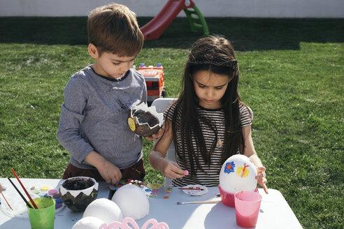 Friends painting Easter eggs in garden - MOMF00691