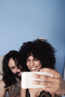 Happy affectionate young couple taking a selfie in bed - IGGF01069