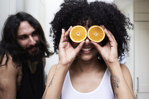 Happy young woman covering her eyes with oranges in kitchen - IGGF01078