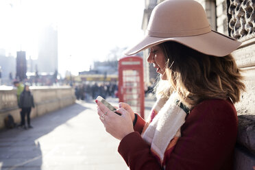 UK, London, woman in the city wearing a floppy hat using cell phone - IGGF01120