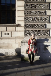 Stylish woman standing at a building using cell phone - IGGF01123