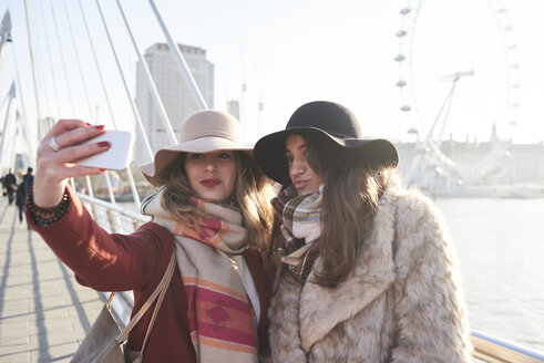 UK, London, two women taking a selfie on Millennium Bridge with London Eye in background - IGGF01135