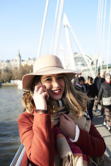 UK, London, stylish young woman talking on cell phone on Millennium Bridge - IGGF01138