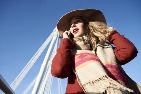 UK, London, stylish young woman talking on cell phone on Millennium Bridge - IGGF01141