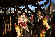 Two happy women having fun on a carousel - IGGF01144