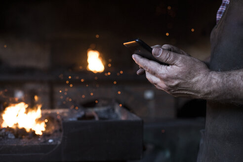 Close-up of blacksmith holding cell phone in his workshop - ABZF02304