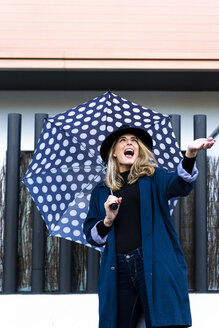 Blond woman with umbrella on a rainy day - ERRF01057
