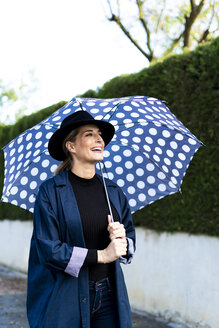 Blond woman with umbrella on a rainy day - ERRF01060