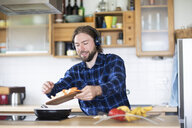 Young man with beard and plaid shirt, and headphones cooking vegetables in kitchen - SGF02363