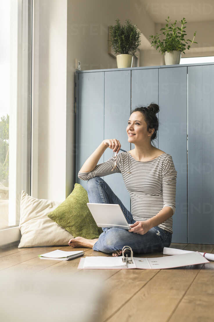 Smiling woman sitting at the window at home working with laptop and file folder - UUF17168 - Uwe Umstätter/Westend61