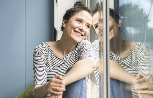 Smiling woman looking out of window at home - UUF17183