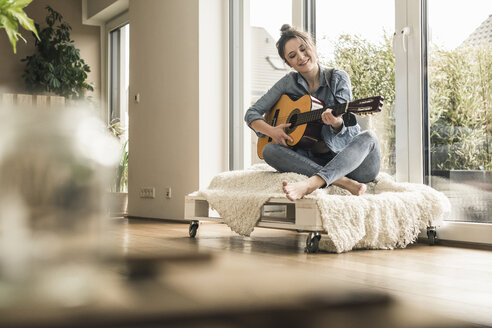 Smiling woman sitting at the window at home playing guitar - UUF17204