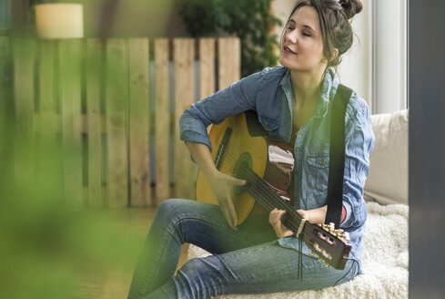 Passionate woman playing guitar at home - UUF17207