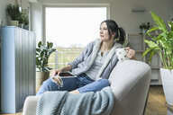 Pensive woman with a mug and tablet sitting on the couch at home - UUF17216