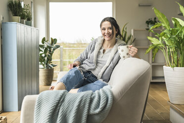 Portrait of happy woman with a mug and tablet sitting on the couch at home - UUF17219