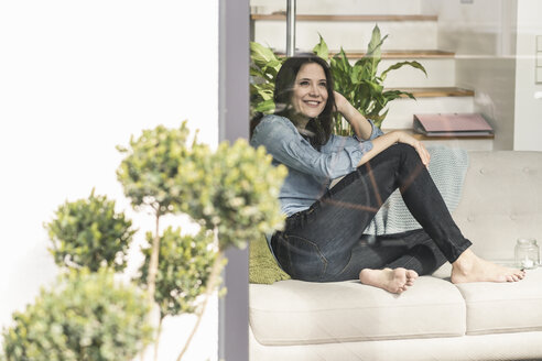 Happy woman sitting on couch behind windowpane at home - UUF17228