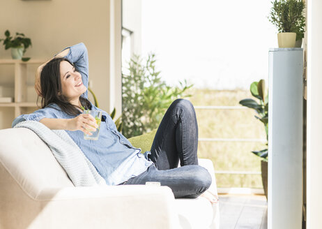 Happy woman with a glass of infused water sitting on the couch at home - UUF17231