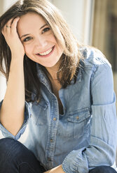 Portrait of happy woman wearing denim shirt at home - UUF17234