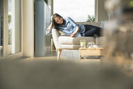 Happy woman lying on the couch at home using tablet - UUF17240