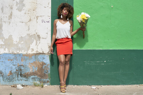 Afro woman on a green and blue wall holding flowers. Baixa, Moçambique, Maputo. - VEGF00003
