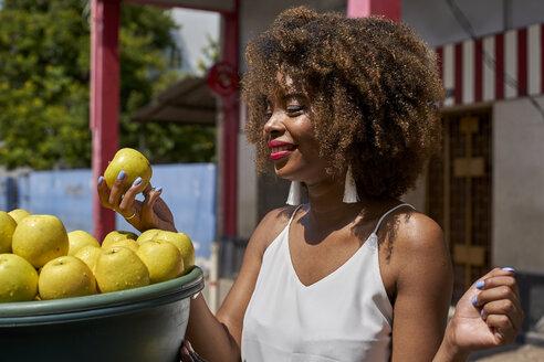 Afro woman choosing apples in the street. Baixa, Moçambique, Maputo. - VEGF00009
