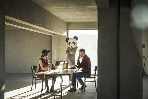 Woman with panda mask watching colleagues in office - MJRF00150