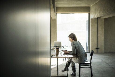 Woman sitting in office, using smartphone - MJRF00174