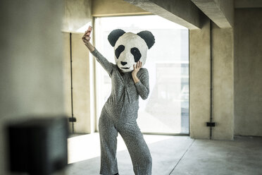 Woman with panda mask standing in office, taking selfie - MJRF00180
