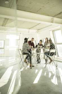 Group of creative professionals having a meeting in a bright office, discussing new solutions - MJRF00183