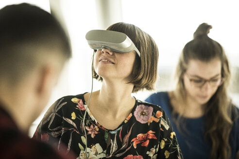 Woman using VR goggles in office - MJRF00186