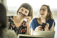 Colleagues having fun in office, making fun with a pencil moustache - MJRF00192
