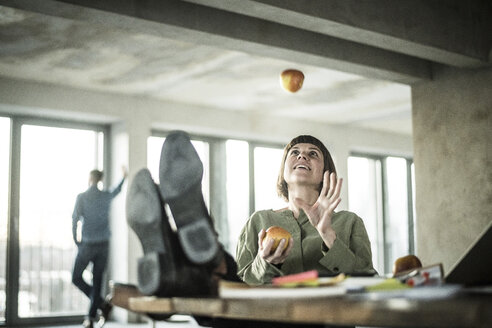Woman juggling apples in the office, sitting with feet on desk - MJRF00204