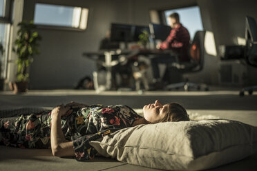 Woman taking a nap, lying on a cushion on the office floor - MJRF00210