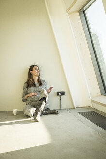 Pregnant woman drinking tea, sitting on floor of her new home - MJRF00213
