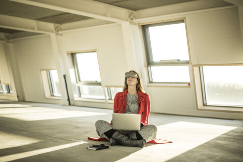 Pregnant busnesswoman sitting on floor of new office rooms, using VR goggles and laptop - MJRF00219