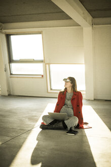 Pregnant busnesswoman sitting on floor of new office rooms, using VR goggles and laptop - MJRF00222