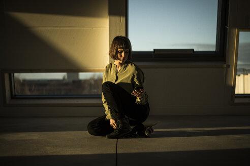 Businesswoman sitting on office floor at sunset, using smartphone - MJRF00228