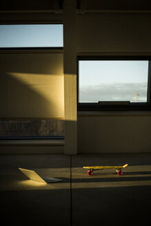 Laptop and skateboard in empty loft office at sunset - MJRF00231