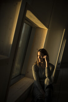 Woman sitting at office window at sunset, talking on the phone - MJRF00237
