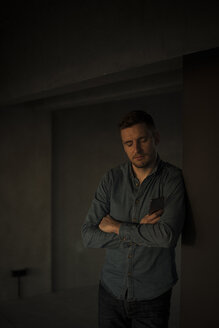 Exhausted businessman leaning on wall, with arms crossed - MJRF00240