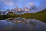 Italy, Trentino, Dolomites, Passo Rolle, Pale di San Martino range, Cimon della Pala with Baita Segantini reflecting in small lake in the evening - RUEF02131