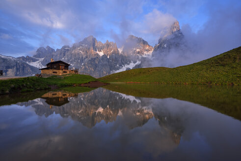 Italy, Trentino, Dolomites, Passo Rolle, Pale di San Martino range, Cimon della Pala with Baita Segantini reflecting in small lake in the evening - RUEF02131