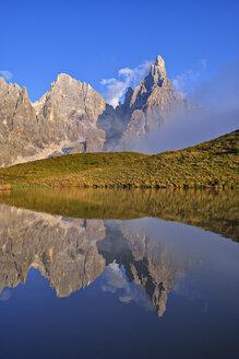 Italy, Trentino, Dolomites, Passo Rolle, Pale di San Martino range, Cimon della Pala with Baita Segantini reflecting in small lake - RUEF02155