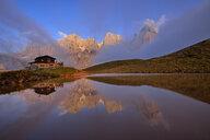 Italy, the mountain group with the mountain Pale di San Martino with Cimon della Pala reflecting in small lake at sunset, Rifugio Baita Giovanni Segantini - RUEF02158